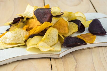 Bunch of delicious, healthy mixed exotic roots chips on a cutting board.