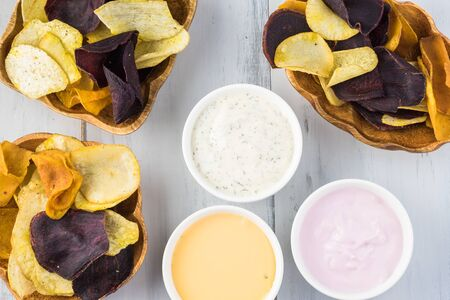 Bowls of delicious, healthy mixed exotic roots chips and healthy dips - dill greek yogurt, strawberry yogurt dips and hot jalapeno cheese dip.