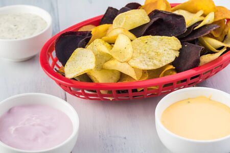Basket of delicious, healthy mixed exotic roots chips and healthy dips - dill greek yogurt, strawberry yogurt dips and hot jalapeno queso dip.