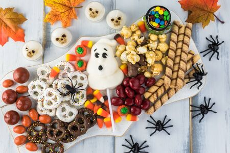 Close up of  board with assorted mixed candies prepared for Halloween celebration.