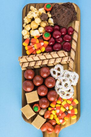 Close up of  board with assorted mixed candies prepared for Halloween celebration on a blue background. Stock Photo
