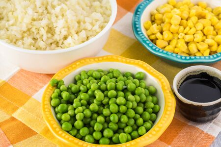 Close up of ingredients for cauliflower fried rice - bowl with cauliflower rice, green peas, bowl with sweet corn. Stock Photo