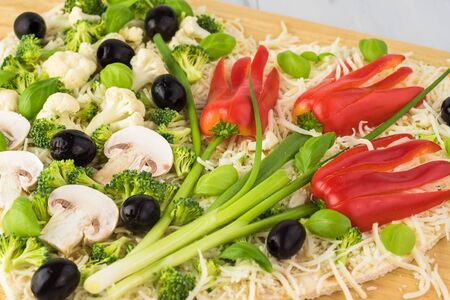 Close up of unbaked colorful heart shaped pizza with vegetables flowers for Valentine Day.