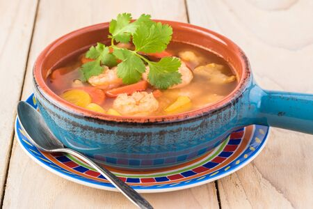 Close up of bowl with mexican spicy shrimp and vegetables soup.