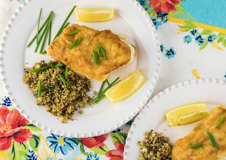 Close up of fried piece of cod fish and mediterranean style quinoa on a white plates.