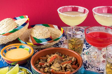 View of fiesta table with food and drink prepared for celebration. Carnitas de Res, Mexican rice, chips and salsa and alcohol drinks.