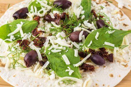 Tortilla filled with feta, mozzarella cheese, baby spinach, fresh dill, sun dried tomatoes, kalamata olives. Imagens