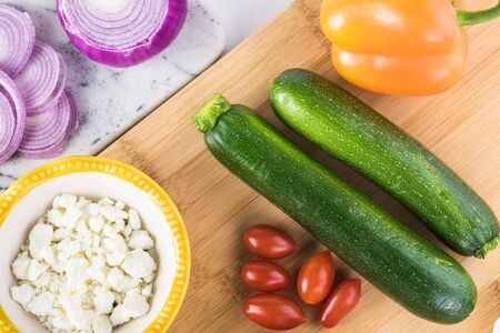 Ingredients for spiral zucchini noodles salad - zucchini, cherry tomatoes, bell pepper, onion, feta cheese, greens.