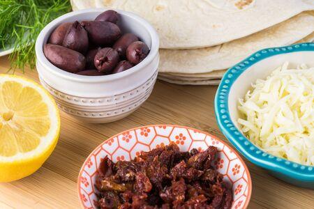 Ingredients for mediterranean style quesadillas - bowl with mozzarella cheese, sun dried tomatoes, kalamata olives, tortillas. fresh dill.