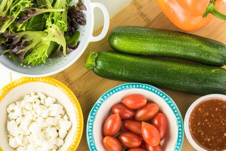 Ingredients for spiral zucchini noodles salad - zucchini, cherry tomatoes, bell pepper, onion, feta cheese, greens. Imagens
