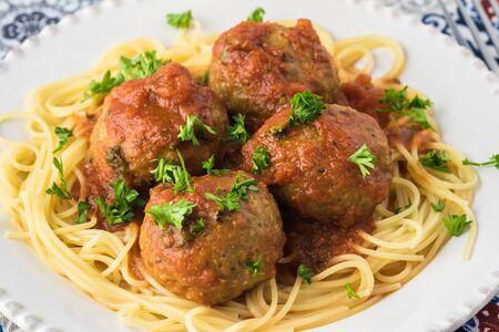 Plate with zucchini spaghetti and meatballs in marinara sauce.