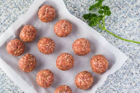 Raw meatballs on a parchment paper - ready to oven.