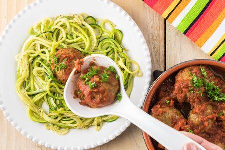 Assiette de spaghettis de courgettes et boulettes de viande à la sauce marinara. Banque d'images