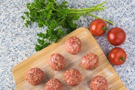Raw meatballs on a cutting board.