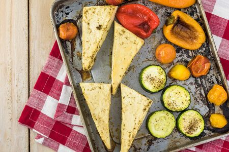 Roasted marinated tofu and vegetables on a baking pan. Imagens