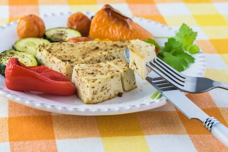 Roasted marinated tofu and vegetables on a white plate.