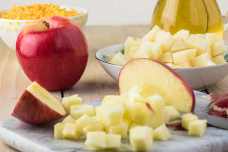 Ingredienta for homemade bacon apple creamy cheese soup. Cut apple on cutting board, cut potatoes.