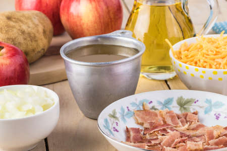 Ingredienta for homemade bacon apple creamy cheese soup. Bowl with cooked bacon, chicken broth, sharp cheddar cheese.