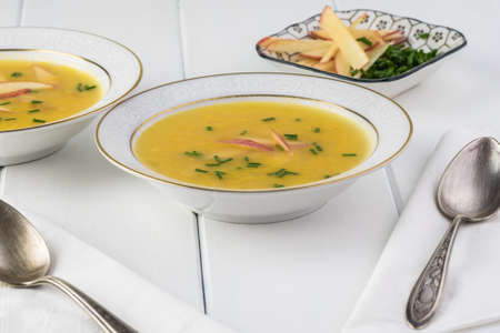 Bowls with homemade bacon apple creamy cheese soup.