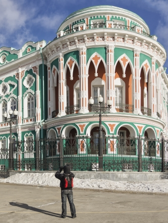 eclecticism: Man takes photo of Sevastyanovs Mansion (1863-1866) in Yekaterinburg, Russia in winter