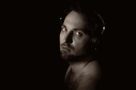 man in shadow: vintage-like low key portrait of young man with beard and hairy shoulders in headphones