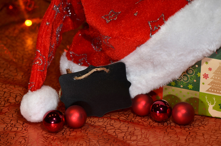 chrstmas: Black sign with space for Chrstmas wishes among decoration with baubles, gift and Santa hat