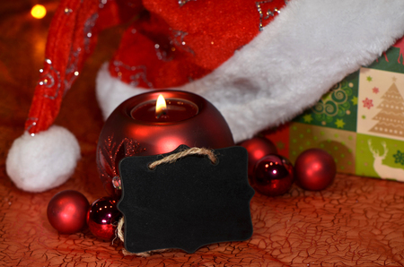 chrstmas: Black sign with space for Chrstmas wishes among decoration with baubles, candle, gift and Santa hat Stock Photo