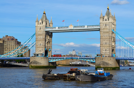 View to the Tower Bridge over the water with boats on a sunny day with a wonderful blue sky - London, Great Britain - 08012015