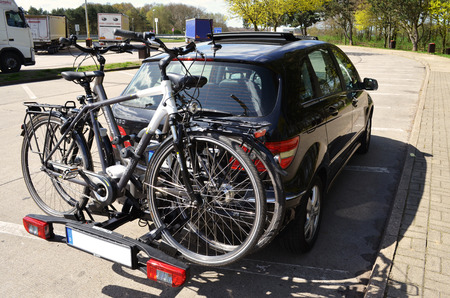 Car with a cycle carrier and two pedelecs on a highway picnic area- highway 24 between Berlin and Hamburg, Germany - 04/20/2016