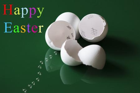 Kleurrijke Pasen-groeten met verbrijzelde eierschalen, bezinningen en sporen van een ontsnapt kuiken voor een groene achtergrond