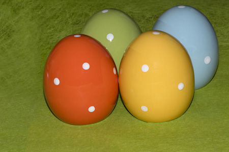 Four colorful ceramic easter eggs in front of a green background with place for Easter greetings