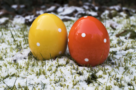 Wintry Easter with colorful ceramic easter eggs which are standing in grass and snow. Stock fotó