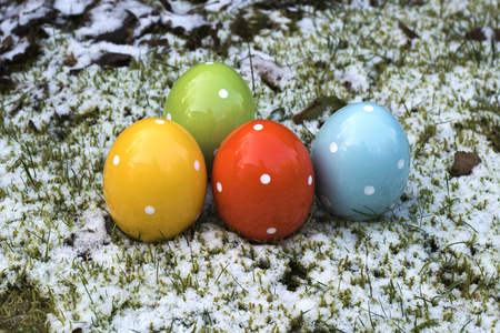 Wintry Easter with colorful ceramic easter eggs which are standing in grass and snow. Stock Photo