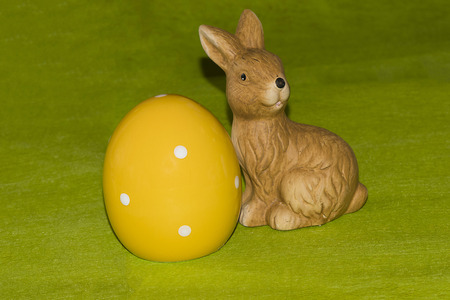 A yellow ceramic easter egg and an Easter bunny in front of a green background Stock Photo