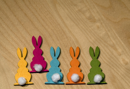Five colorful wooden Easter bunnies in a row and one of them is dancing out of line - space for own text