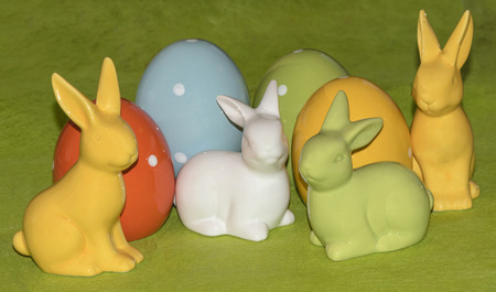 Four colorful ceramic easter eggs and four  Easter bunnies in front of a green background