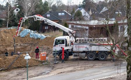 家の地下室を作る作業エリア上の労働者と移動式コンクリートポンプ - ベルリン、ドイツ - 03/09/2018
