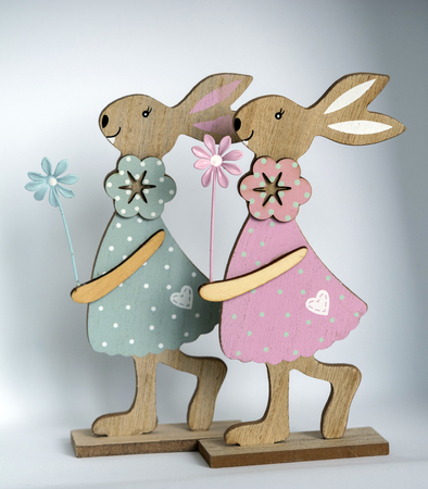 Two wooden Easter bunnies with painted decoration and parts of wire in front of a bright background