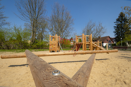 Sand with various wooden playground equipment on a public playground in Berlin
