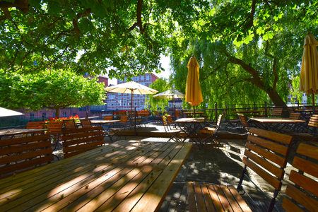 Lueneburg, Germany - June 5, 2018: View into a beer garden with various wooden garden furniture and sunshades under trees.