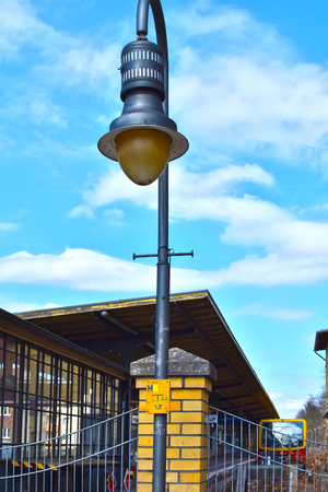Berlin, Germany - April 02, 2018: View of an old Berlin S-Bahn station in the district of Lichtenrade with a lantern in foreground and a train in the background Editorial