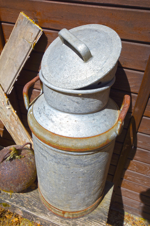 Old milk jug on the wooden wall of a shed in bright sunlight Stock Photo