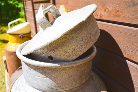 Two old milk churns on the wooden wall of a shed in bright sunlight Stock Photo