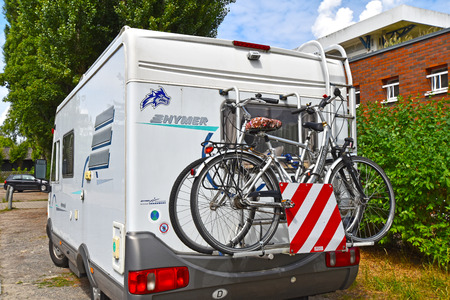 Berlin, Germany - June 16, 2018: A white motorhome with a cycle carrier attached to the rear, with two bicycles
