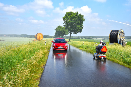 Near Uelzen, Germany - June 4, 2018: Electromobility - Electric wheelchair meets an electric hybrid vehicle on a rural road