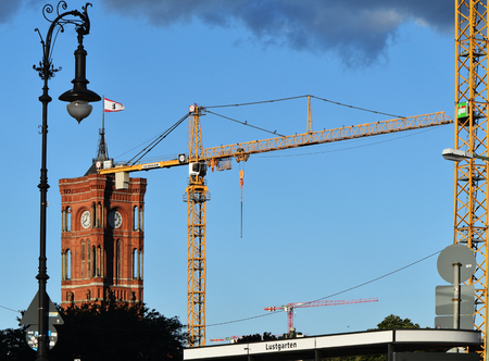 Berlin, Germany - June 30, 2018: View from the Lustgarten onto the tower of the Red Town Hall and a historic lantern in Berlin. You can also see cranes from the construction sites of downtown. Banque d'images - 115644293