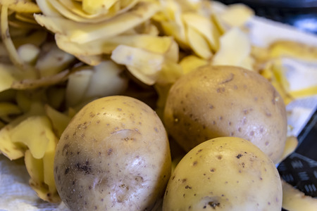 Three potatoes in the foreground and potato peels for the compost in the background.