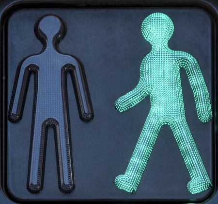 Symbols of a pedestrian traffic light, of which the green is lit to indicate walking. Imagens