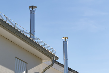 Two stainless steel chimneys and parts of a roof in front of a bright blue sky. Standard-Bild - 118156645