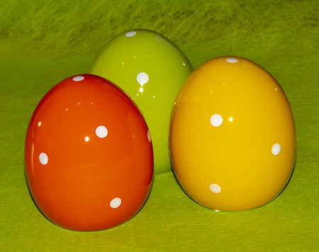 Colorful ceramic easter eggs in front of a green background Reklamní fotografie